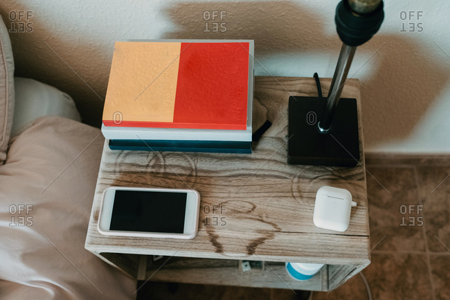 From above notebooks and smartphone in composition with true wireless earphones and lamp on wooden bedside table in cozy bedroom of modern apartment