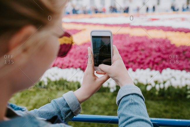 Crop faceless female traveler in jeans shirt and sunglasses taking photo of colorful big flowerbed on mobile phone while standing near fencing and looking at screen