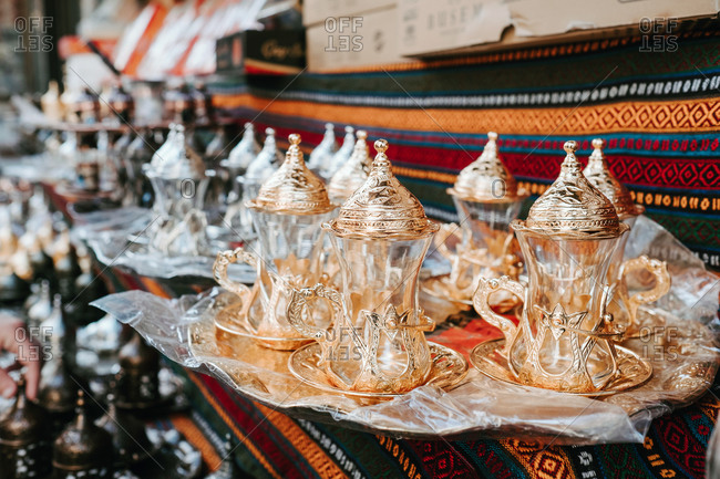 Set of glass traditional Turkish teapots with golden ornaments composed on tray on patterned oriental fabric at market in Istanbul