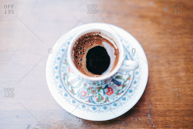 From above of aromatic black hot Turkish coffee in fragile traditional white cup and saucer painted with oriental pattern standing on wooden table