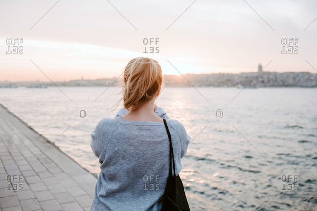 Back view of anonymous female traveler in casual outfit standing on embankment and admiring view of colorful amazing sunset