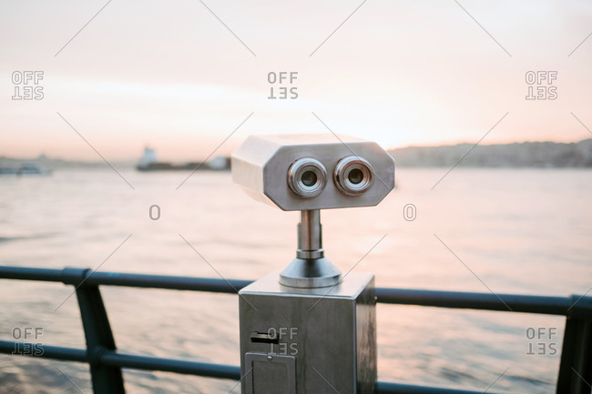 Amazing landscape of gray steel binocular locating on observation platform near black fencing against background of calm sea water reflecting and marvelous light pink sunset sky