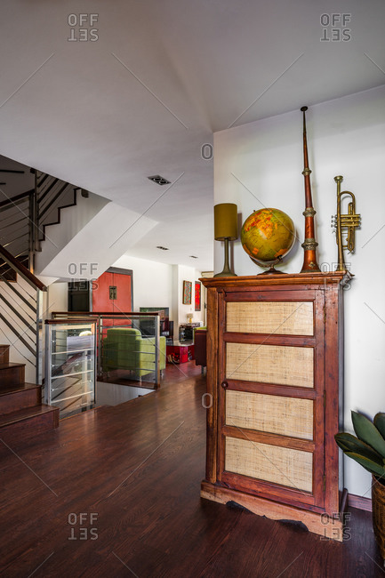 Fragment of interior of spacious house with retro wooden furniture decorated with musical instruments and globe