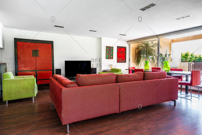 Modern living room interior in red and green colors with large couch and chairs placed on laminate floor against white wall