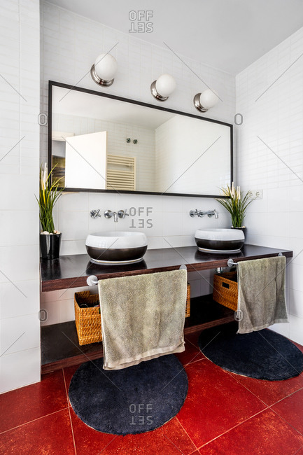 Modern bathroom with lamps and large mirror placed over stylish counter with sinks and cozy round carpets on red floor