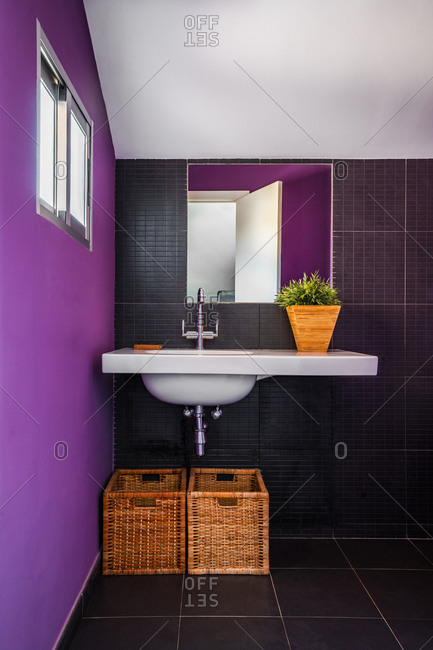 Modern bathroom with colorful purple wall with large mirror placed over stylish white rectangular counter sink with straw baskets underneath