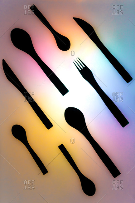 Top view composition of black cutlery set arranged on illuminated neon multicolored surface