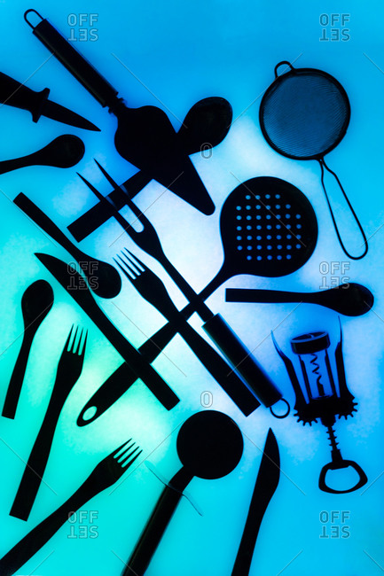 Top view of various essential cooking tools and cutlery placed chaotically on illuminated blue background