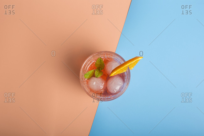 Top view of alcohol cocktail with ice cubes and sprig of mint in glass placed on colorful background with orange slice