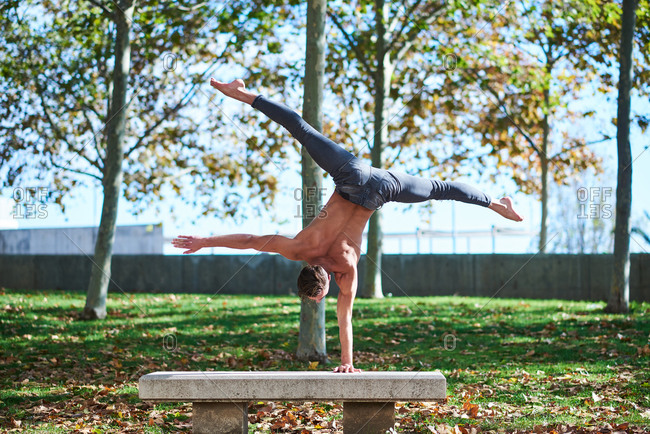 Back view of unrecognizable shirtless guy in jeans doing handstand with legs spread wide on concrete gray bench in autumn park with fallen leaves