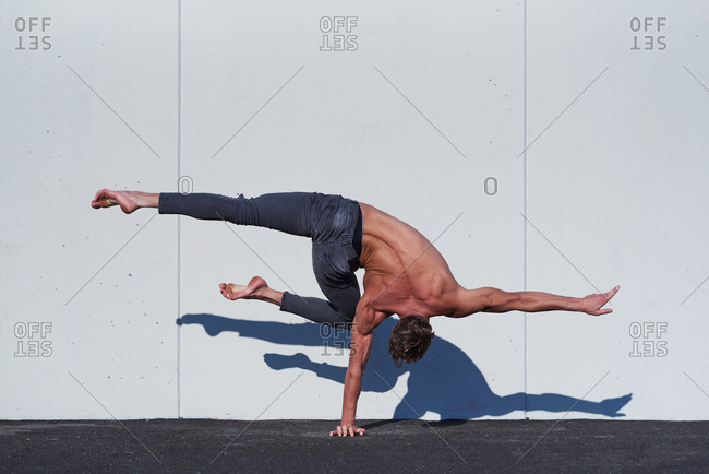 Back view of faceless muscular shirtless acrobat standing on one hand while stretching one leg perpendicular to floor and other bending at knee during training against white wall