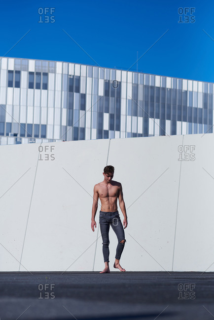 Shirtless sportsman resting after performance standing against wall with blue clear sky on rooftop of modern building