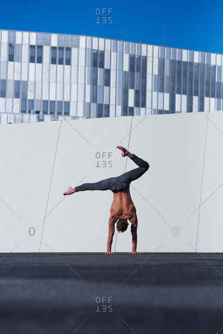 Back view of unrecognizable shirtless sportsman performing handstand with one hand while doing exercises against wall and blue sky on rooftop of modern building