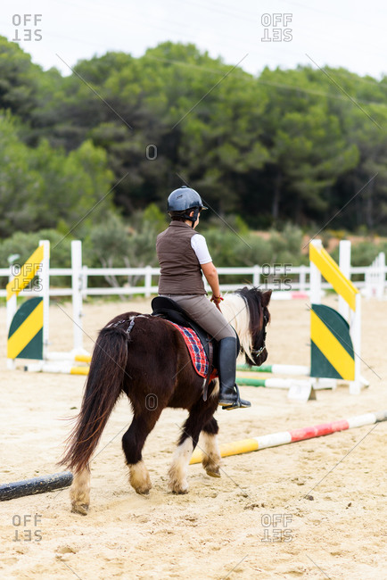 Back view of unrecognizable teen boy jockey in helmet riding brown horse on dressage arena during training in equestrian school