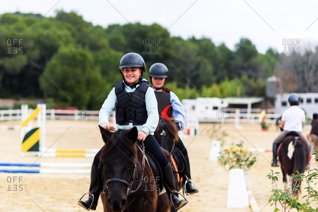 Happy teen jockeys in helmets riding obedient horses on sandy dressage arena during lesson in equestrian school