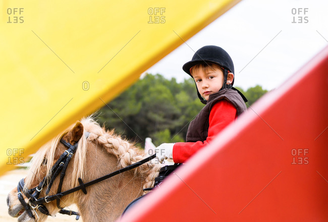 Side view of little jockey in helmet looking at camera while riding pony with braided mane behind red and yellow barrier on dressage arena
