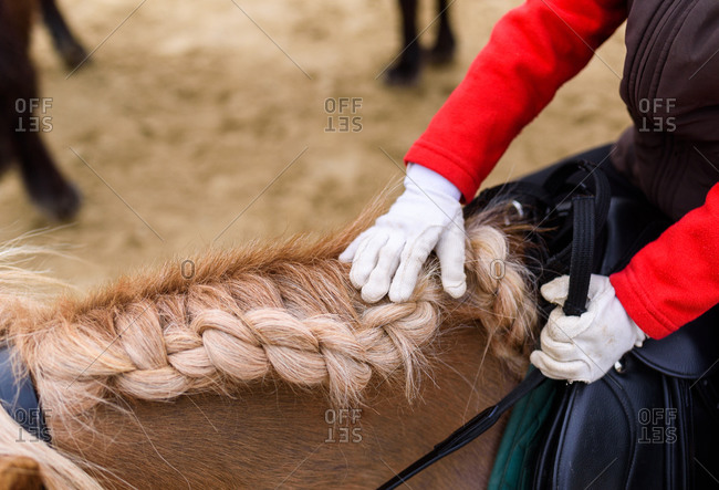 From above anonymous kid in jockey costume and gloves touching braided mane while riding pony on arena during training in equestrian school