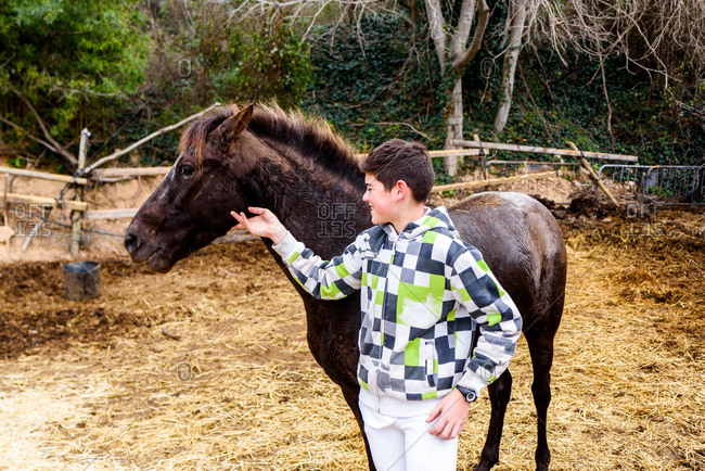 Cheerful teen boy in checkered hoodie smiling and touching head of brown horse while standing in paddock after training in equestrian school