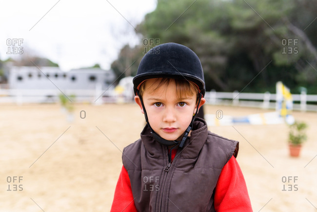 Cute little jockey in helmet and waistcoat looking at camera while standing on blurred background of paddock of equestrian school