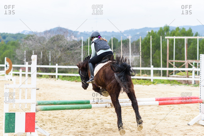 Back view of unrecognizable teen girl in helmet sitting on horse back and jumping over hurdle during training on dressage arena of equestrian school