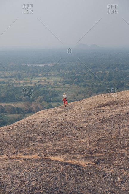 From above back view of unrecognizable traveling female in casual clothes walking downhill on background of valley with forest and lake during summer holiday in Sigiriya