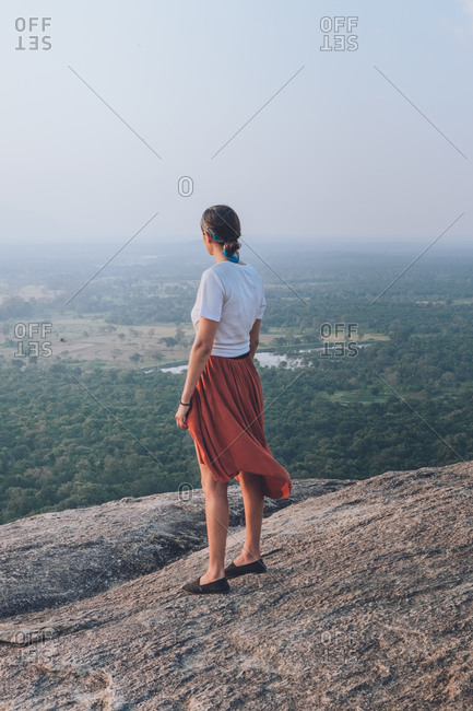 Side view of unrecognizable traveling female in casual clothes standing in a rocky hill on background of valley with forest and lake during summer holiday in Sigiriya