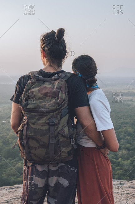 Back view of unrecognizable content couple of hipsters in casual clothing hugging traveling together around Sri Lanka enjoying majestic landscapes