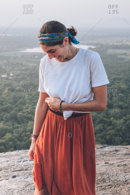 Serene traveling woman in casual clothes and bandana admiring scenic landscape during vacation in Sigiriya while standing in back lit and looking away