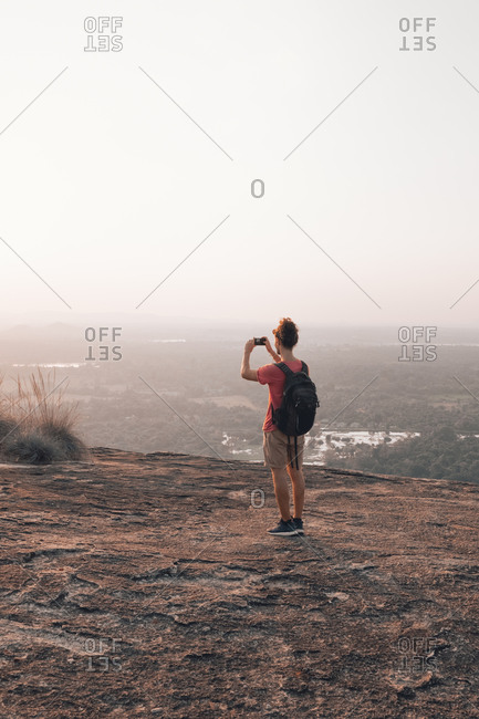 Back view of young unrecognizable male traveler in casual clothes with haversack standing on edge of cliff and taking picture of majestic landscape of green forest against cloudless blue sky during sunset