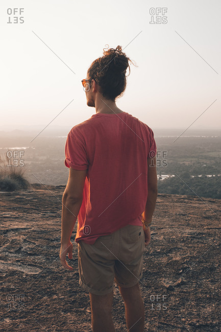 Back view of young man in casual outfit standing on rocky cliff and admiring incredible view against cloudless sky during sunset