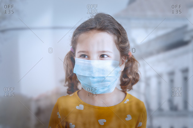 Through glass view of little girl with pigtails in protective mask wearing colorful yellow clothes standing in medical room and looking away