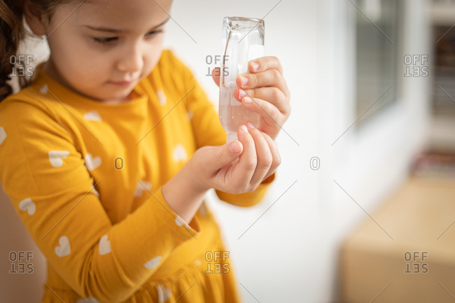 Serious little girl wearing yellow colorful dress standing in medical room and pouring antiseptic liquid from plastic bottle on hands