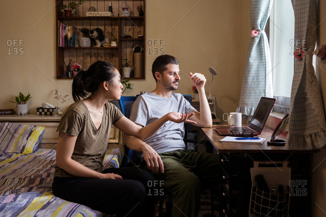 Young couple in casual clothes sitting in bedroom at table and using computer together while discussing video