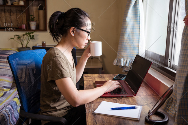 Side view of Asian female freelancer in casual t shirt and eyeglasses sitting at table and browsing computer while working on project online at home and drinking hot beverage from a mug