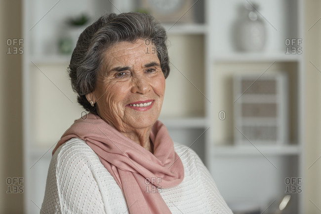 Happy elderly woman in pink scarf looking at camera while staying at home during coronavirus pandemic