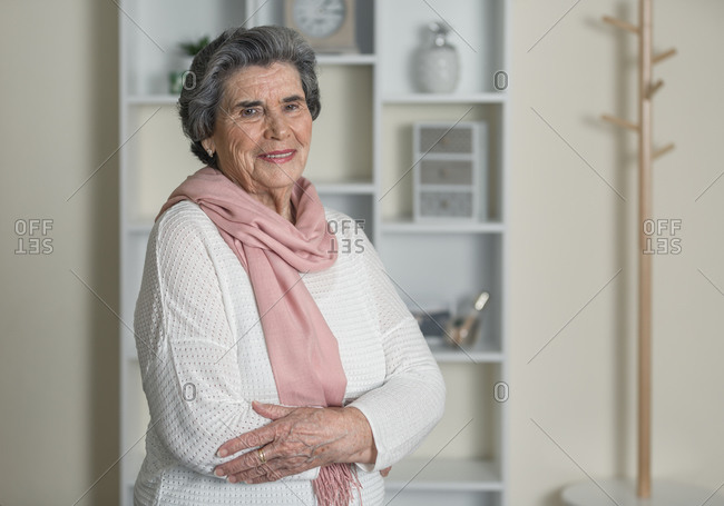 Elderly woman in pink scarf looking at camera with arms crossed while staying at home during coronavirus pandemic