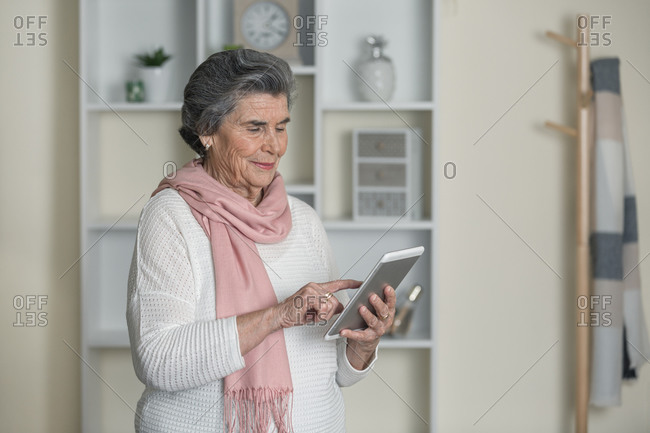 Friendly elderly lady with contemporary tablet in cozy room at home