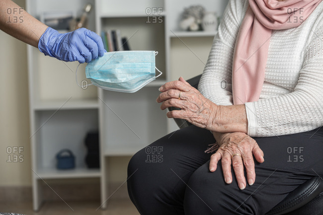 Crop unrecognizable social worker in latex gloves giving a medical mask to a elderly female on chair while taking care of pensioner during coronavirus pandemic at home