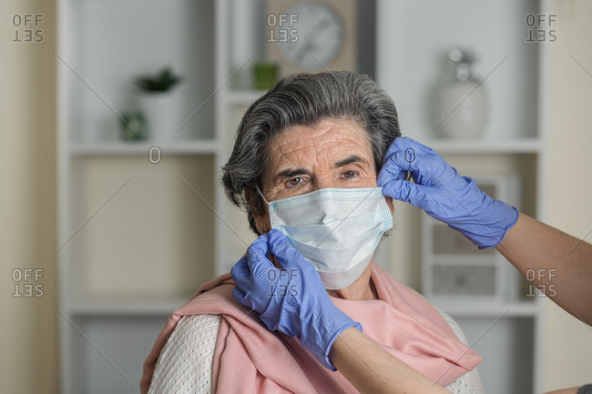 Crop anonymous social worker in latex gloves putting on medical mask on elderly female on chair while taking care of pensioner during coronavirus pandemic at home
