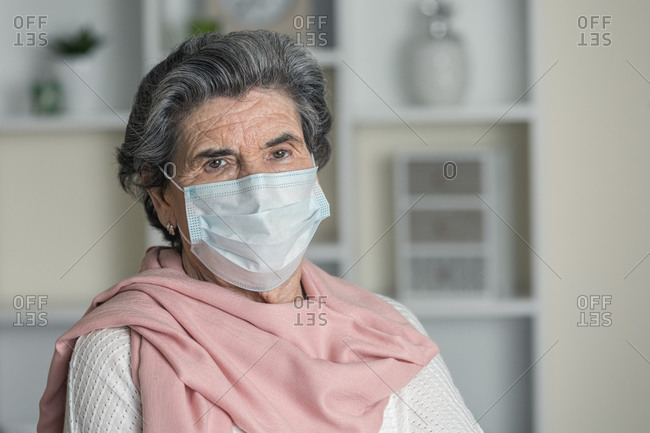 Elderly woman in medical mask and pink scarf looking at camera while staying at home during coronavirus pandemic