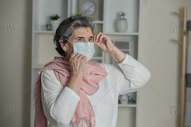 Elderly woman in medical mask and pink scarf looking away while staying at home during coronavirus pandemic
