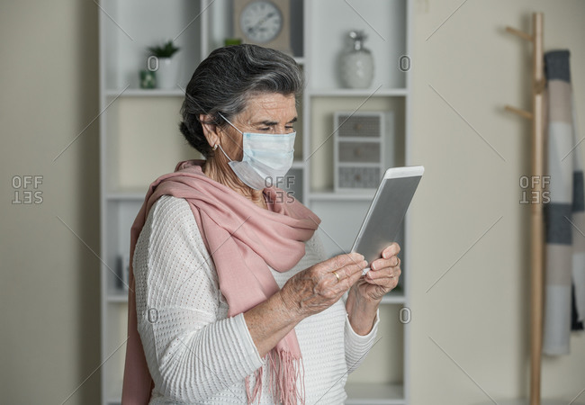Senior female with medical mask using video chat app on smartphone during coronavirus pandemic at home