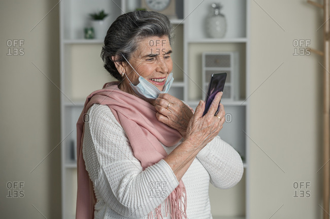 Happy senior female taking off medical mask and smiling while using video chat app on smartphone during coronavirus pandemic at home