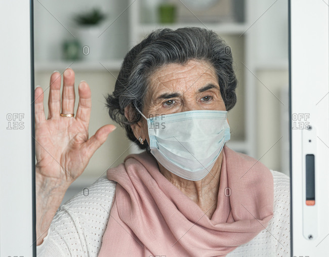 Elderly lady in medical mask waving looking away throughout the windows while staying at home during coronavirus epidemic