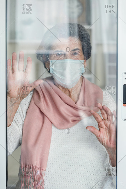 Elderly lady in medical mask waving looking at camera throughout the windows while staying at home during coronavirus epidemic