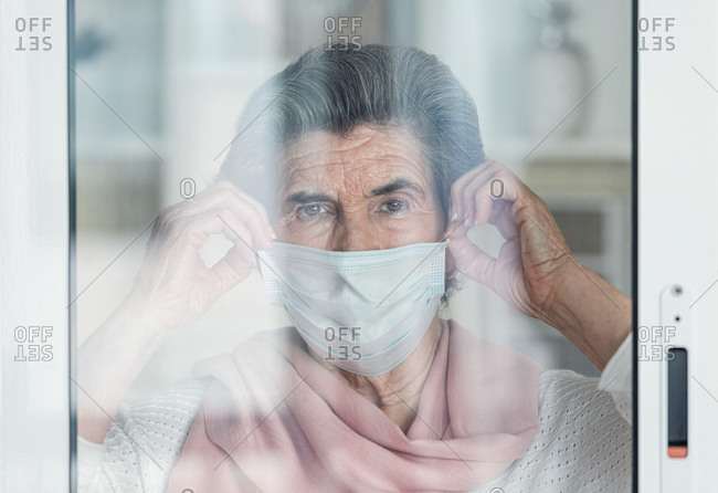 Sad elderly lady in medical mask touching glass and looking at camera throughout window while staying at home during coronavirus epidemic