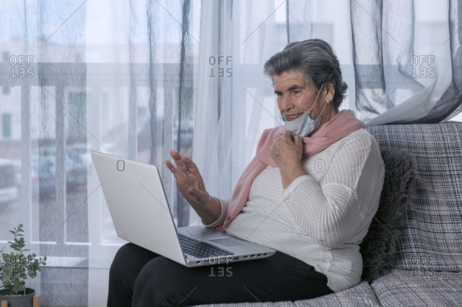 Senior female in medical mask sitting on couch and doing video call through laptop while staying at home during coronavirus pandemic