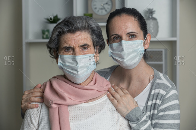 Senior mother and daughter in casual clothes and medical mask looking at camera while staying at home during coronavirus pandemic