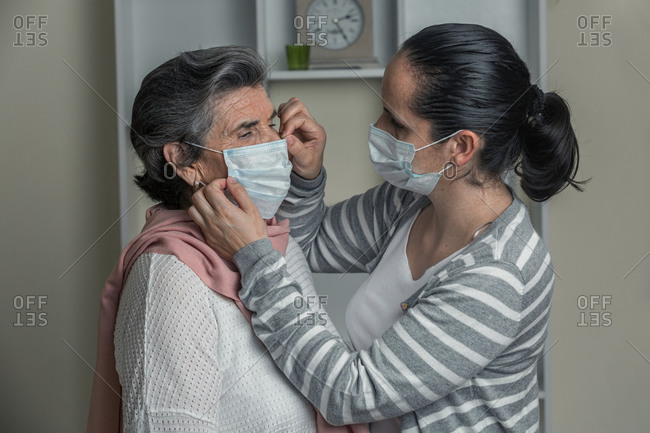 Young female in casual clothes putting on medical mask on senior woman from risk group while staying at home during coronavirus pandemic