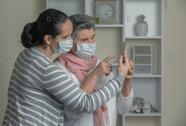 Grandmother and granddaughter in medical mask using mobile phone to call to relatives while staying at home during coronavirus epidemic